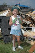 stock photo of katrina  - young girl holding a water bottle in front of some rubble removed from her house - JPG