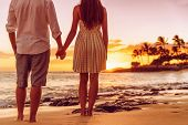 Beach couple watching sunset holding hands. People from behind relaxing enjoying summer travel vacat poster
