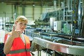 Portrait Female Employee In Orange Robe Vest In Working Space Of Production Facility, Supervises And poster