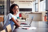 Young black woman in office with laptop smiling to camera poster