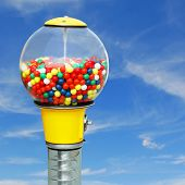 stock photo of gumball machine  - Gumball machine with colorful chewing gum balls on square blue sky background - JPG