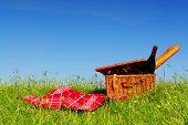 Постер, плакат: Пикник корзина с вином и хлеб на траве с фоном голубого неба
