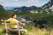Traveler Mountains Rest Bench. Young Traveler Mountains Is Resting Sitting Wooden Bench. Hot Summer  poster