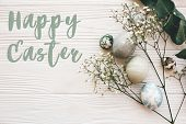 Happy Easter Text Sign On Stylish Easter Eggs With Spring Flowers And Green Branch On White Wooden T poster