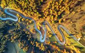 Winding Road In Autumn Forest At Sunset In Mountains. Aerial View. Top View Of Beautiful Asphalt Roa poster