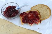 Raspberry Preserves In A Crystal Bowl Next To Wheat  Bread Spread With The Preserves. All On Butcher poster