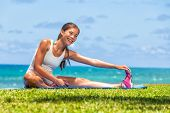 Fitness woman stretch legs doing warm-up before run workout training outdoor. Asian athlete stretchi poster