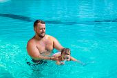 Dad Teaches A Child To Swim In The Pool. Father And Child Having Fun In The Pool. Dad And Daughter S poster