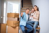Cheerful Husband Pointing With Finger And Smiling While Sitting On Stairs Near Wife And Daughter In  poster