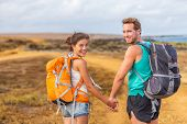 Happy young couple tourists in love holding hands walking on trek hike with backpacks. Hikers on nat poster
