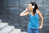 stock photo of rap-girl  - Young happy sportive woman in urban background listening music - JPG