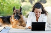 stock photo of black curly hair  - Young happy woman with her dog and laptop - JPG