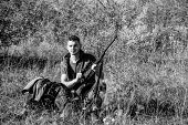 Hunter With Rifle Looking For Animal. Hunter Khaki Clothes Ready To Hunt Nature Background. Hunting  poster