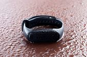 Fitness Bracelet On The Table. Bracelet Poured With Water On A Wooden Surface. poster
