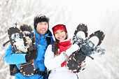 Winter couple happy outdoor hiking in snow on snowshoes. Healthy lifestyle photo of young smiling ac