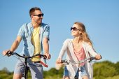 people, leisure and lifestyle concept - happy young couple riding bicycles in summer poster