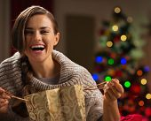 Happy Woman With Shopping Bag In Front Of Christmas Tree