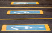 stock photo of physically handicapped  - Row of parking spaces with a handicapped sign - JPG