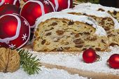 stock photo of walnut-tree  - Slices of traditional Christmas Stollen  cake with dried fruit and icing with red tree decorations alongside  - JPG