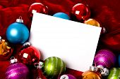 picture of christmas party  - A group of colorful Christmas baubles or ball surrounding a white note card with copy space - JPG