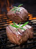 stock photo of braai  - closeup of steaks on a grill - JPG