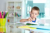 picture of diligent  - Serious schoolkid drawing with pencil in copybook - JPG
