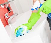 stock photo of stereotype  - Woman cleaning sink and faucet in bathroom at home - JPG