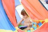 Cute baby having happy playful time in colorful tent on beach