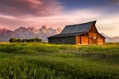 stock photo of fog  - Early morning sunshine illuminating the iconic Moulton barn and Teton peaks in Grand Teton National Park WY - JPG