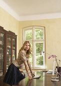 pic of shelving unit  - Side view of a young woman leaning on study table at home - JPG