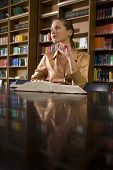 picture of shelving unit  - Thoughtful young woman with book sitting at desk in library - JPG