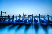 stock photo of gondola  - Venice gondolas or gondole on a blue sunset twilight and San Giorgio Maggiore church landmark on background - JPG