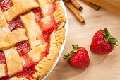 stock photo of fancy cakes  - Homemade strawberry rhubarb pie with Strawberries and cinnamon on a wooden cutting board - JPG