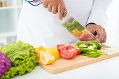 stock photo of food crops  - Cropped image of a professional cook slicing pepper on the cutting board - JPG