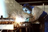 stock photo of flux  - Factory worker welding metal in a factory showing sparks and protective gear - JPG