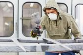 Man in protective clothes and respirator works in paint-spraying booth, painting car details