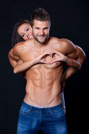 stock photo of breast-stroke  - A young woman stands behind a muscular young man embraces him hands and shows fingers heart - JPG