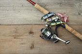 stock photo of bass fish  - lot of colorful lures with the fishing rod on the wooden pier - JPG