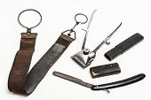 picture of barber razor  - Old and worn rusty razor razor case sharpening leather and a metal trimmer on a white background - JPG