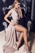 pic of silver-hair  - beautiful glamour woman with blond hair in beige silk dress sitting on the black armchair - JPG
