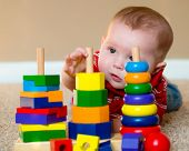 image of playgroup  - Baby boy playing with stacking learning toy - JPG