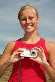 Happy Young Woman Holding Digital Camera poster