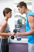stock photo of lifting-off  - Fit couple lifting dumbbells together facing off at the gym - JPG