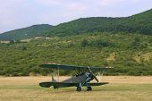 picture of biplane  - A vintage camouflage biplane secured to the ground at a grassy airfield