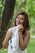 stock photo of breather  - Pretty young woman wiping the sweat by a white towel in the park - JPG