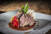 picture of duck breast  - Plate with slices of duck breast on a wooden table - JPG