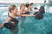 picture of day care center  - Smiling female fitness class doing aqua aerobics with foam dumbbells in swimming pool at the leisure centre - JPG