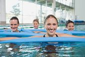 image of day care center  - Female fitness class doing aqua aerobics with foam rollers in swimming pool at the leisure centre - JPG