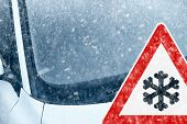 pic of ice-scraper  - Snow on an ice covered windshield with warning sign - JPG