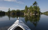 stock photo of calm  - Selective focus on the kayak bow on a calm bay on a northern lake with island reflections on the water - JPG